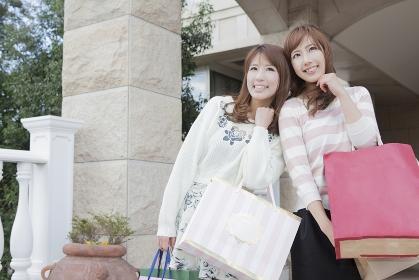 友達とショッピングバッグを持って同じ方向を見つめる女性