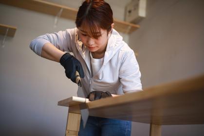 ノコギリで木を切る女性 DIYイメージ