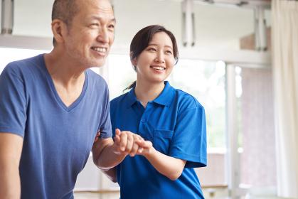 高齢者の歩行介助をする介護士