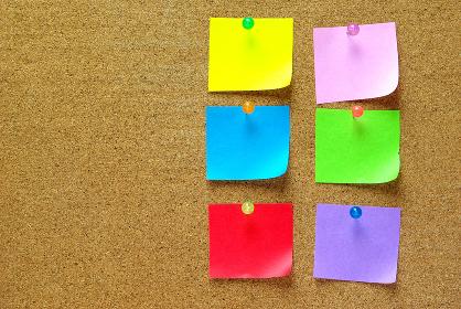 コルクボードにピンで留めた色紙を裂いた6枚のメモ紙とコルクボードの余白