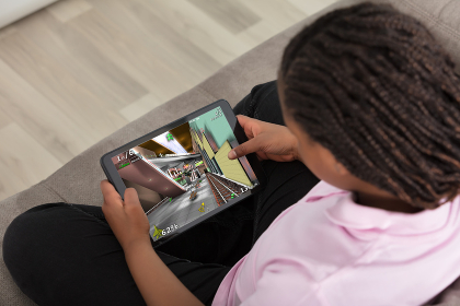 Girl Playing Video Game On Digital Tablet