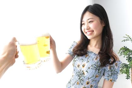ビアガーデンでビールを飲む若い女性