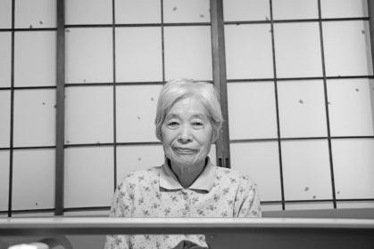障子窓の前の介護用ベッドに座って真顔でこちらを見る白髪のおばあちゃん