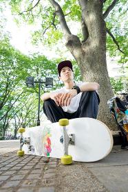 スケートボードの練習を休憩する男性