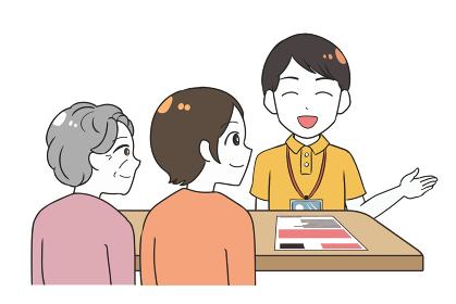 笑顔で説明する男性介護士 祖母と娘