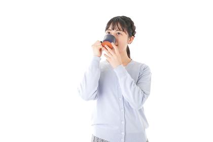 マグカップでコーヒーを飲む若い女性