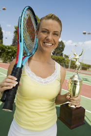 Woman on tennis court with Tennis Rackets and Trophy portrait
