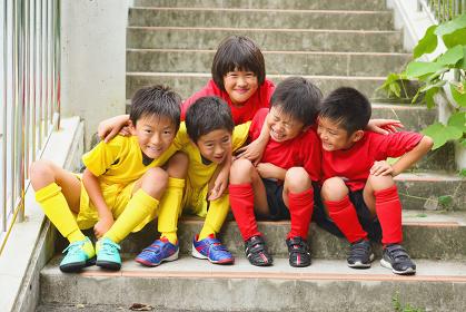 階段に座るサッカー少年