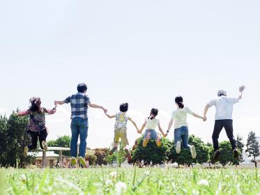 晴れた公園で手をつなぎジャンプする三世代家族