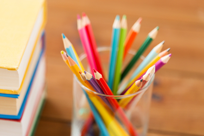 close up of crayons or color pencils and books