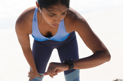 Mixed race woman exercising on beach checking smartwatch. healthy outdoor leisure time by the sea.