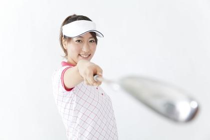 ゴルフクラブを向ける女性