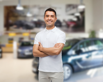 smiling man in white t-shirt over  auto salon
