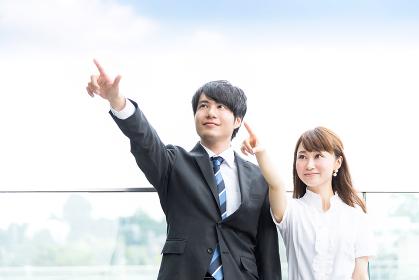 指差しをする男女(ビジネスイメージ)