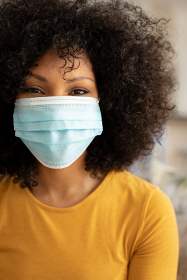 Portrait of African American woman with afro hair at home, wearing a mask and looking to camera. Social distancing and self isolating at home during Coronavirus Covid 19 quarantine lockdown.