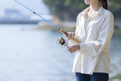 海辺で釣りを楽しむ若い女性