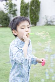 シャボン玉で遊ぶ男児