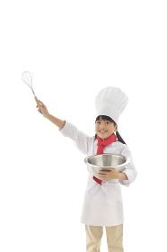 泡立て器を持つ女の子のシェフ