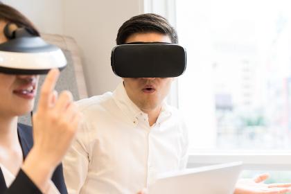 VRゴーグルを装着して仕事をする人々(驚く男性)