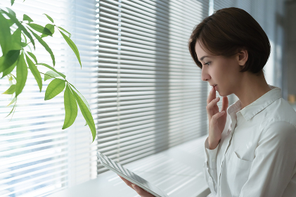 窓際でタブレットPCを見る若い女性