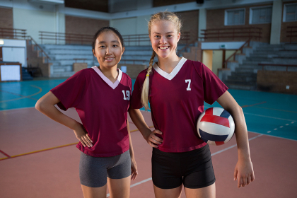 Female players standing together with ball in the volleyball court