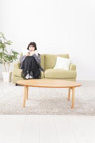 家でテレビを見る若い女性