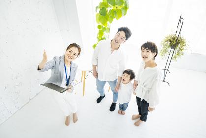 不動産の業者からインテリアの説明を受ける家族