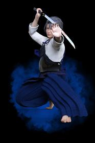 剣道の道着を着た若い男性が日本刀を持ち低い姿勢で真剣な表情で構えている
