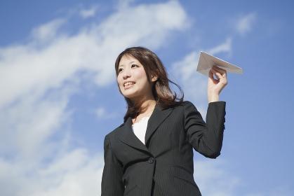 紙飛行機を飛ばすビジネスウーマン