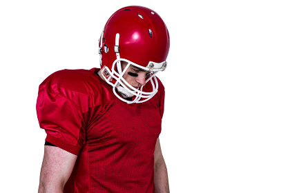 Unsmiling american football player looking down