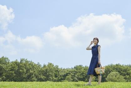 青空の下を歩く日本人女性