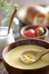 木目の板にある朝食のセットとコーンポタージュスープ