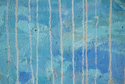 くすんだ青色のペイントに垂れた跡の線が付いている古いコンクリートの壁