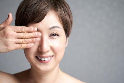 片目を隠す中年の日本人女性
