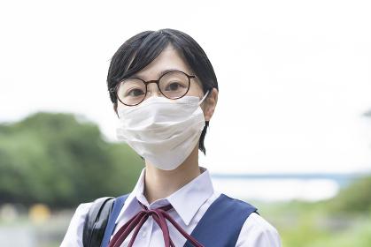 マスクを装着して通学する女子高生