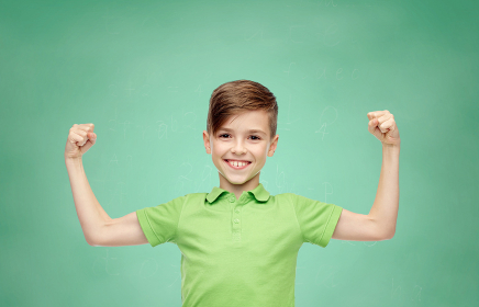 happy boy in polo t-shirt showing strong fists