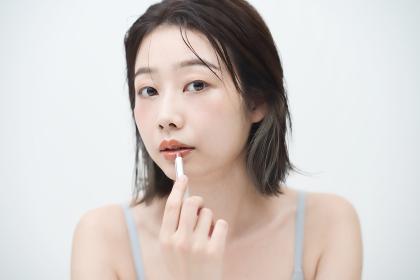 口紅を唇に塗る若い女性