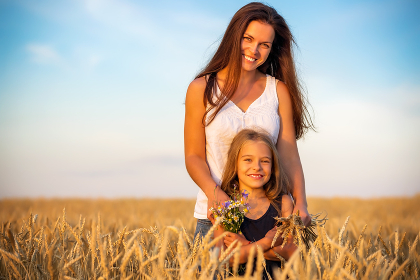 Young mother and her daughter standing on wheat field at sunset.