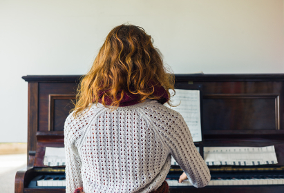 A young woman is playing the piano