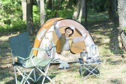 ソロキャンプイメージ・テントの中から笑顔で手を振る若い女性