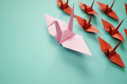 複数の茶色で小さな折り鶴を率いているピンクの大きな折り鶴。左に青緑のスペースがある。