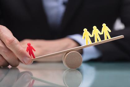 Businessperson Showing Imbalance Between Figures On Seesaw