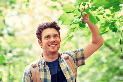 smiling young man with backpack hiking in woods