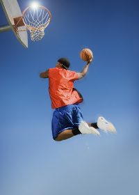 Man Dunking Basketball Into Hoop Against Blue Sky