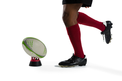 Low section of sportsman kicking rugby ball on tee