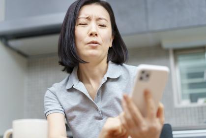 疲れた表情でスマートフォンを持つ女性