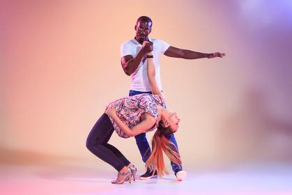 Young couple dances social Caribbean Salsa, studio shot