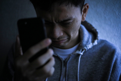 スマートフォンを手に持ち涙を流す男性