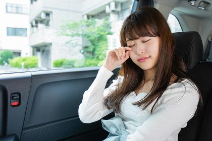 後部座席で寝る女性