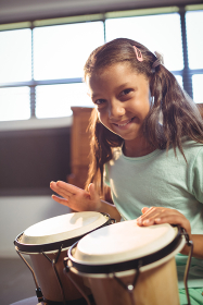 Portrait of smiling girl playing bongo drums